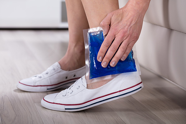 Close-up Of Woman's Hand Holding Cool Gel Pack On Her Ankle