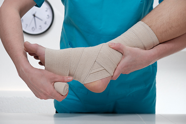Close-up of female doctor bandaging foot of male patient at doctor's office.