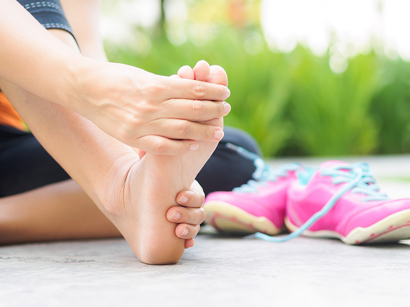 Soft focus woman massaging her painful foot while exercising.   Running sport injury and healthcare concept.